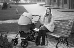 Foto blanco y negro de la madre que se sienta en banco con strol del bebé Imagenes de archivo