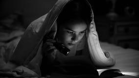Foto blanco y negro de la muchacha que miente debajo de la manta y del libro de lectura con la linterna Imagen de archivo libre de regalías
