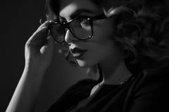 Foto blanco y negro de la secretaria joven atractiva en vidrios y cur fotos de archivo