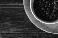 Foto blanco y negro de los granos de café en una taza en backgro de madera Imagen de archivo libre de regalías