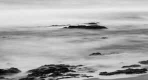 Foto blanco y negro de rocas en el mar Fotos de archivo libres de regalías
