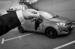 Foto blanco y negro del hombre en el traje que lleva a cabo llaves del coche contra el ne Fotos de archivo libres de regalías