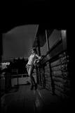 Foto blanco y negro, lejos mujer que se coloca en una barra en los vaqueros, esperando, oscuridad, sitio de madera Fotos de archivo