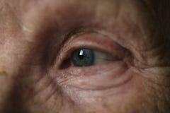 Foto blu-grigia del primo piano dell'occhio della donna anziana Immagini Stock