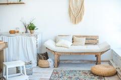 A foto bonita da mola do interior da cozinha na luz textured cores Cozinha, sala de visitas com o sofá bege do sofá, grande cacto fotografia de stock