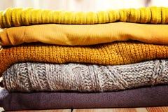 Foto bonita de uma pilha de camisetas feitas malha da mulher amarela Forma da mulher Roupa do outono Fotos de Stock Royalty Free