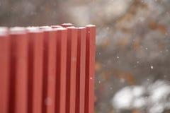 Foto borrada da neve que cai na cerca vermelha imagem de stock