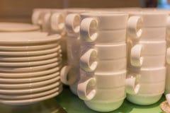 Foto borrosa de las tazas blancas que apilan con la preparación de las placas bien Fotografía de archivo libre de regalías