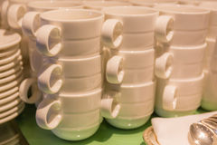 Foto borrosa de las tazas blancas que apilan con las placas y las cucharillas nosotros Imagen de archivo