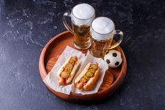 Foto bovenop twee glazen bier en hotdogs op houten dienblad met voetbal royalty-vrije stock foto