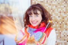 Foto brillante al aire libre de la muchacha sonriente feliz hermosa joven con las luces en manos, al aire libre El modelo mira pa Fotos de archivo libres de regalías