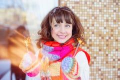 Foto brillante al aire libre de la muchacha sonriente feliz hermosa joven con las luces en manos, al aire libre El modelo mira pa Imágenes de archivo libres de regalías
