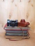 Foto-cámara vieja de la película del vintage con el caso de cuero en fondo de madera Imagen de archivo