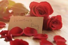 Foto caliente de tres rosas rojas con los pétalos en la tabla de madera y la tarjeta de papel para el día de tarjetas del día de  Fotografía de archivo