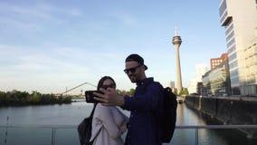 Foto caucásica feliz del beso de la sonrisa de los pares que presenta la cámara del teléfono, Düsseldorf, Alemania almacen de video