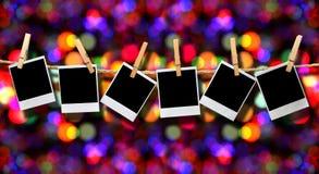 Foto che appendono su una corda con la priorità bassa di festa Fotografia Stock