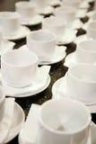 Foto che sta molto attentamente insieme le file diagonali 16 tazze bianche della porcellana Fotografie Stock