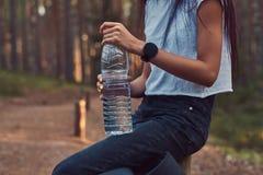 A foto colhida de uma menina do moderno do turista guarda uma garrafa da água, parada para descansar em uma floresta bonita do ou foto de stock
