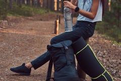 A foto colhida de uma menina do moderno do turista guarda uma garrafa da água, parada para descansar em uma floresta bonita do ou imagens de stock royalty free
