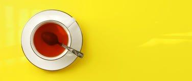 Foto colocada lisa - o copo branco da porcelana com colher encheu o chá ambarino quente, na placa amarela, espaço largo da band imagem de stock