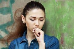 Foto común de una muchacha contra la pared azul Fotografía de archivo
