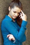 Foto común de una muchacha contra la pared azul Imagen de archivo