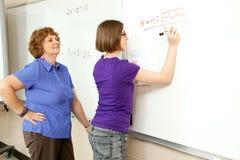 Foto común del estudiante y del profesor en la pizarra Imagenes de archivo