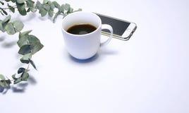 Foto común diseñada Aún la composición femenina de la vida con la taza de café, de teléfono y de ramo de eucalipto ramifica encen Imagen de archivo
