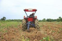 Foto común: El granjero era condujo el tractor que araba el suelo al picup fotos de archivo