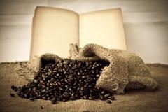 Foto común: Granos de café con el libro viejo del vintage Imagenes de archivo