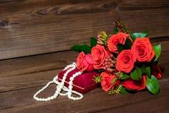 Foto com rosas e pérola no fundo de madeira fotos de stock