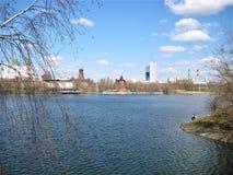 Foto com um fundo da paisagem em um dia de mola e um pescador com uma vara de pesca em uma lagoa de Moscou Fotos de Stock Royalty Free