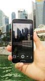Foto con el teléfono móvil en la estatua y el paisaje urbano de Merlion Imagenes de archivo
