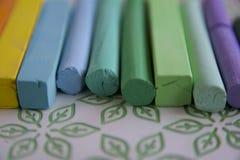 Foto con un gruppo di bastoni dei pastelli artistici con una predominanza delle tonalità verdi dei pastelli adatto a fondo royalty illustrazione gratis