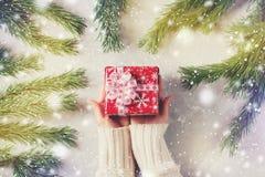 Foto conceptual de la Navidad - la mano femenina guarda la caja con el regalo Fotografía de archivo