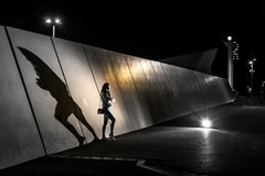 Foto conceptual de la silueta de la mujer joven que se coloca al lado de la pared en la noche Fotos de archivo