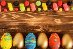 Foto conceptual de Pascua con los huevos y color cendy en fondo de madera Fotos de archivo