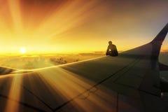 Foto conceptual del viaje de la aventura de la silueta del hombre que se sienta en el destino de Wing Watching Stunning Sunset Wo foto de archivo libre de regalías
