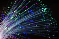 Foto concettuale astratta dei fili della fibra che emettono luce con la luce multicolore Priorità bassa nera fotografia stock libera da diritti