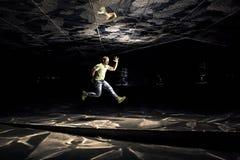 Foto concettuale di giovane ed uomo attraente nel salto su fondo nero Fotografia Stock