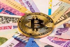 Foto concettuale di internazionalismo del bitcoin Bitcoin fisico della moneta sulle banconote dei paesi differenti Fotografia Stock Libera da Diritti