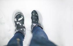 Foto concettuale di inverno con neve circa il tempo Stivali di inverno su uno strato spesso bianco di neve fotografia stock