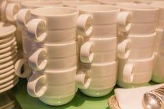 Foto confusa delle tazze bianche che impilano con i piatti ed i cucchiaini noi Immagine Stock