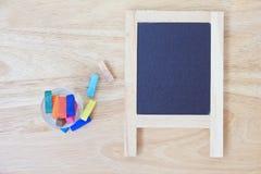Foto conservada em estoque: Ainda vida com quadro-negro vazio e gizes coloridos Imagens de Stock