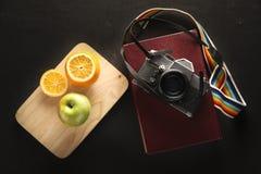 Foto conservada em estoque: a câmera do filme do vintage 35mm e o livro velho Imagens de Stock Royalty Free