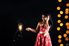 Foto conservada em estoque da menina indiana que guarda o biscoito do fulzadi ou da faísca ou do fogo na noite do diwali imagens de stock