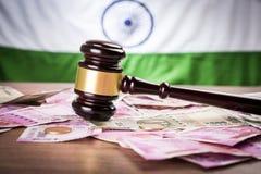 Foto conservada em estoque de notas indianas da rupia da moeda com o martelo da lei isolado no branco, conceito que mostra a lei  Imagem de Stock
