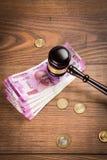 Foto conservada em estoque de notas indianas da rupia da moeda com o martelo da lei isolado no branco, conceito que mostra a lei  Fotografia de Stock