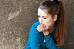 Foto conservada em estoque de uma menina de encontro à parede azul foto de stock