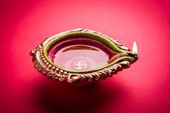 Foto conservada em estoque do diya do diwali ou lâmpada da argila sobre o fundo vermelho, diwali feliz Fotos de Stock Royalty Free